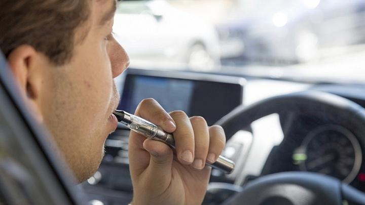 Mann raucht im Auto E-Zigarette