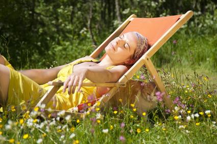 Junge Frau in einem Liegestulh liegend, sonnt sich auf einer sommerlichen Blumenwiese. Unter dem Liegestuhl ein roter kater, totale Idylle.